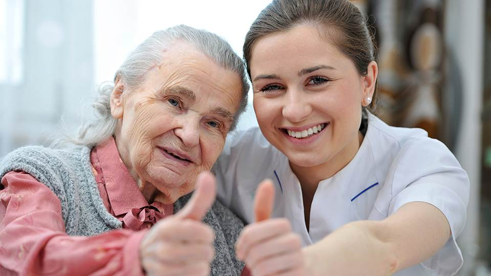 Nurse and elderly woman giving thumbs up