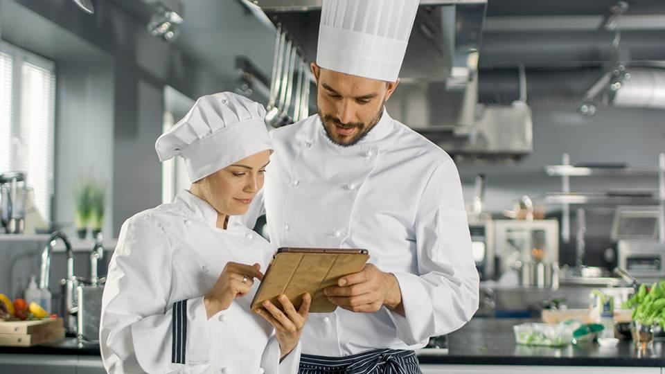 Two chefs looking at tablet screen