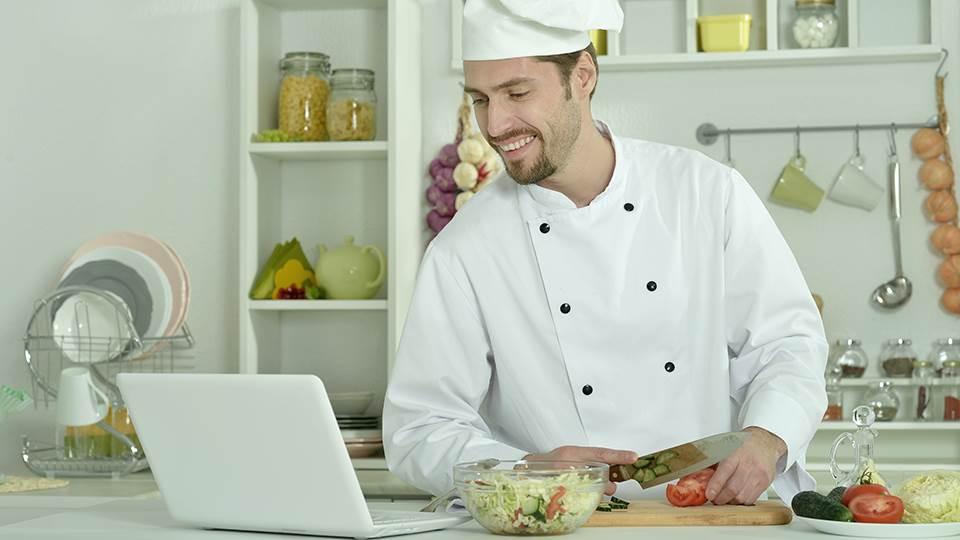 chef in kitchen with computer