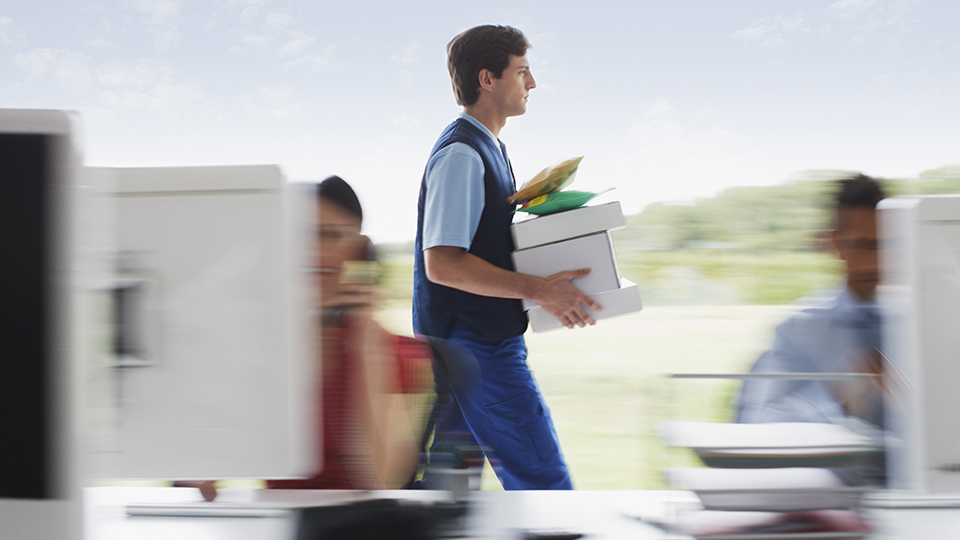worker carrying boxes in office