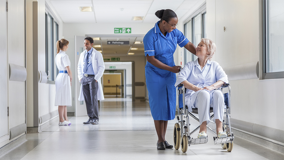 nurse and elderly woman in wheelchair in hopsital
