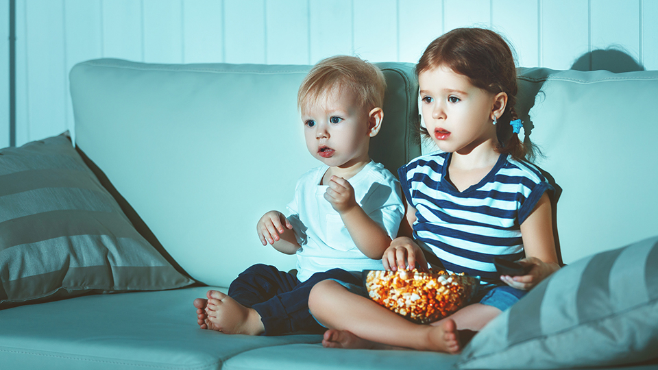 children watching television with popcorn