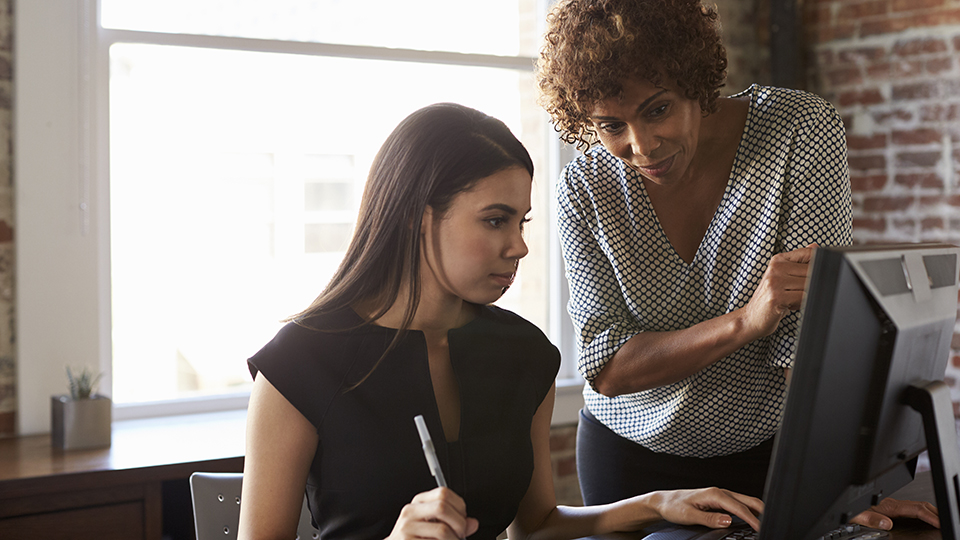 Two business women looking at computer