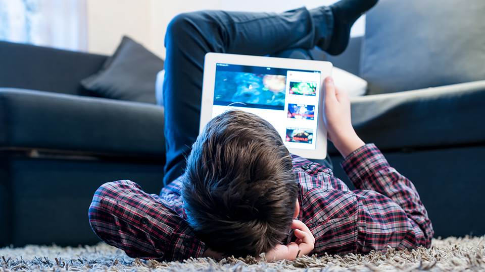 young boy lying on floor with tablet