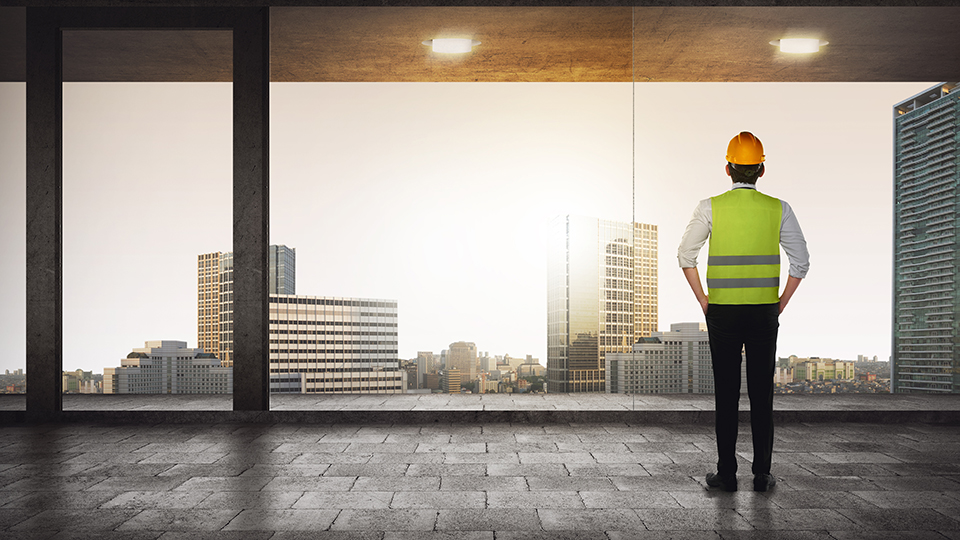 construction worker looking at buildings