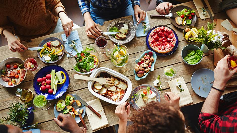 Friends eating at a table of food