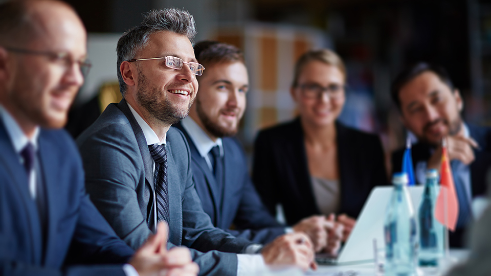 man smiling amongst colleagues in business meeting