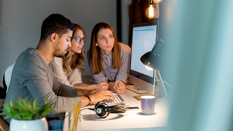 small business team gathered around computer