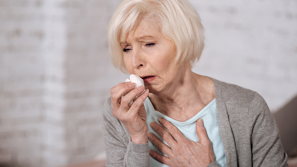 Sick lady coughing into a tissue